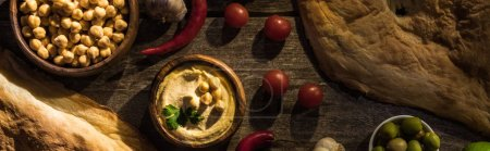 top view of delicious hummus, chickpeas, pita, vegetables and olives on wooden rustic table, panoramic shot