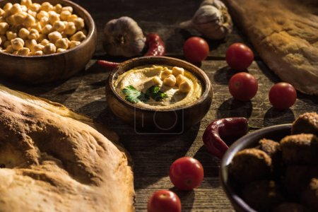 delicious falafel, hummus, chickpeas, pita, vegetables and spices on wooden rustic table