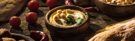 delicious hummus, chickpeas, pita, vegetables and spices on wooden rustic table, panoramic shot
