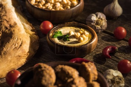 selective focus of falafel and delicious hummus, chickpeas, pita, vegetables and spices on wooden rustic table