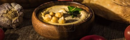 Photo for Delicious hummus, chickpeas, pita, garlic on wooden rustic table, panoramic shot - Royalty Free Image