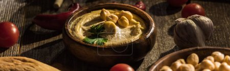 Photo for Delicious hummus, chickpeas, pita, vegetables and spices on wooden rustic table, panoramic shot - Royalty Free Image