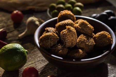 selective focus of delicious falafel balls near lime, black and green olives on wooden rustic table