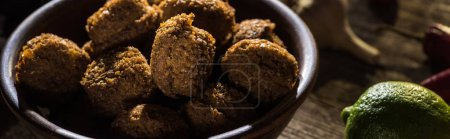 Photo for Delicious falafel balls near lime on wooden rustic table, panoramic shot - Royalty Free Image