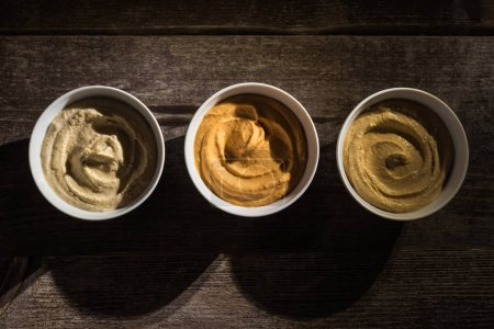 Photo for Top view of delicious assorted hummus on wooden rustic table - Royalty Free Image