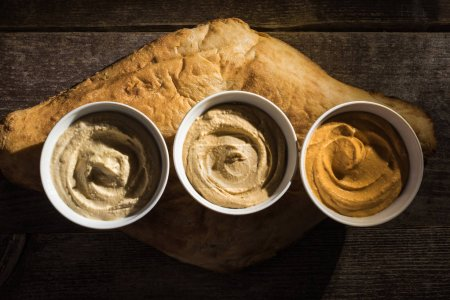 Photo for Top view of delicious assorted hummus on fresh baked pita on wooden rustic table - Royalty Free Image