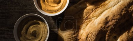 Photo for Top view of delicious assorted hummus near fresh baked pita on wooden rustic table, panoramic shot - Royalty Free Image