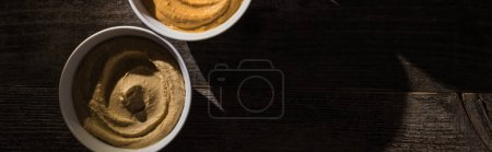 top view of delicious assorted hummus on wooden rustic table, panoramic shot