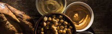 top view of delicious assorted hummus, chickpeas and fresh baked pita on wooden rustic table, panoramic shot