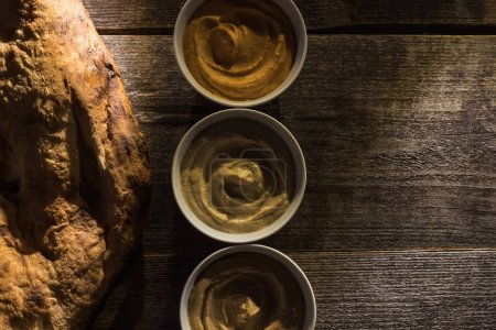 Photo for Top view of delicious assorted hummus and fresh baked pita on wooden rustic table - Royalty Free Image