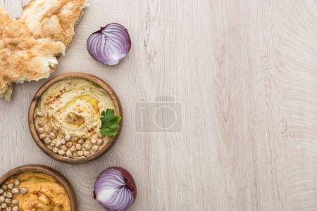 vista superior del delicioso hummus con garbanzos en un tazón cerca de la pita recién horneada, cebolla roja sobre una mesa de madera beige