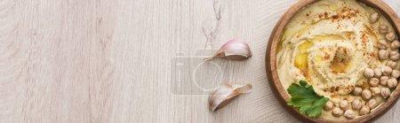 Photo pour Vue du dessus de délicieux houmous aux pois chiches dans un bol près de l'ail sur une table en bois beige, vue panoramique - image libre de droit