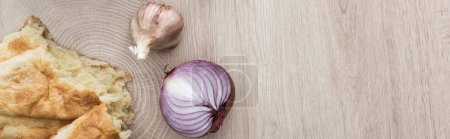 Photo for Top view of delicious fresh baked pita, garlic and red onion on beige wooden table, panoramic shot - Royalty Free Image