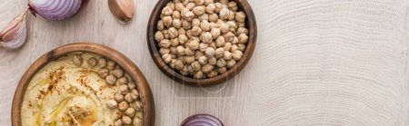 Photo for Top view of delicious hummus with chickpeas in bowl near garlic and red onion on beige wooden table, panoramic shot - Royalty Free Image