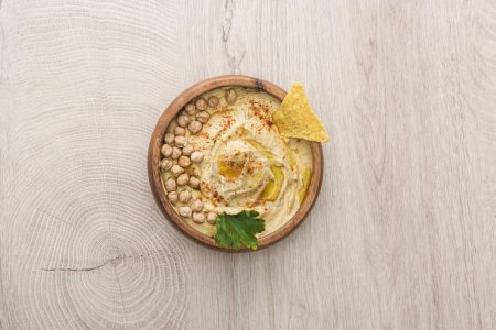 Photo for Top view of delicious hummus with chickpeas and nacho in bowl on beige wooden table - Royalty Free Image