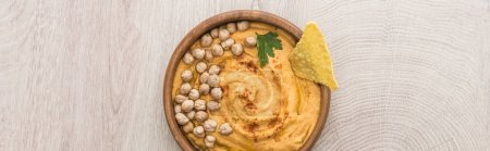 Photo for Top view of delicious hummus with chickpeas and nacho in bowl on beige wooden table, panoramic shot - Royalty Free Image