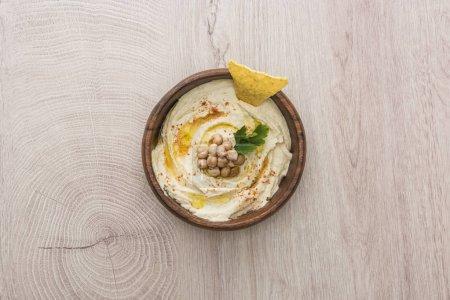 vista superior del delicioso hummus con garbanzos y nacho en tazón sobre mesa de madera beige