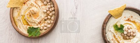 Photo for Top view of delicious hummus with chickpeas and nachos in bowls on beige wooden table, panoramic shot - Royalty Free Image