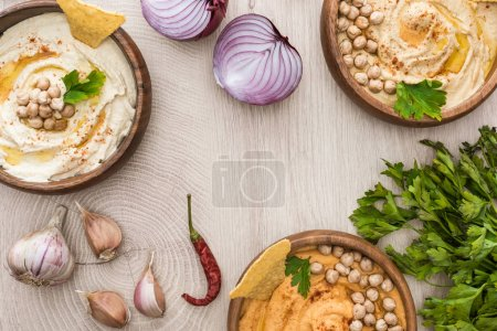 Photo for Top view of delicious hummus with chickpeas, nachos in bowls near spices and parsley on beige wooden table - Royalty Free Image