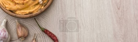 Photo for Top view of delicious hummus with chickpeas in bowl near garlic and chili pepper on beige wooden table, panoramic shot - Royalty Free Image