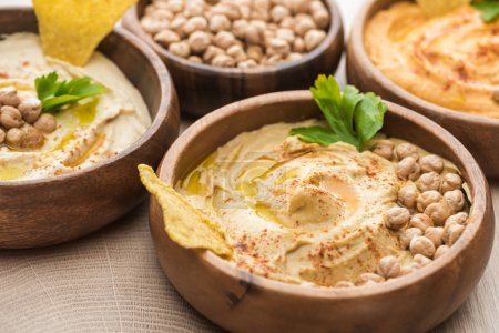 Photo for Close up view of delicious hummus with chickpeas and nacho in bowls on beige wooden table - Royalty Free Image