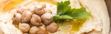 vista de cerca del delicioso hummus con garbanzos en un tazón, plano panorámico