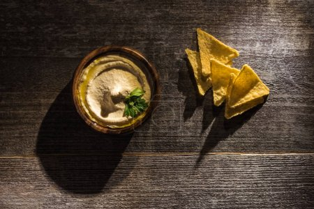Photo for Top view of delicious hummus with corn nachos on wooden rustic table - Royalty Free Image