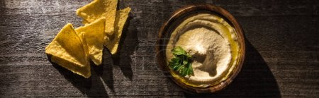 Photo for Top view of delicious hummus with corn nachos on wooden rustic table, panoramic shot - Royalty Free Image