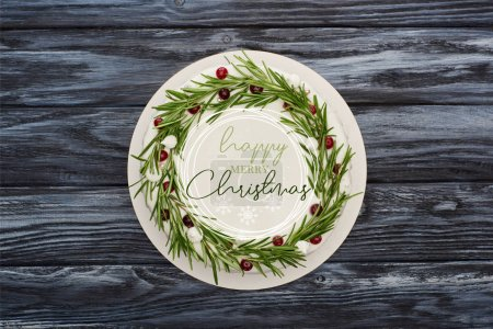 Photo for Top view of traditional christmas pie with white icing, rosemary and cranberries on dark wooden table with happy Merry Christmas illustration - Royalty Free Image