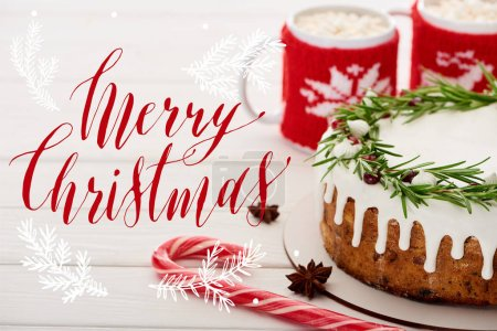 candy cane, christmas pie with icing and two cups of cocoa with marshmallows on white wooden table with Merry Christmas illustration