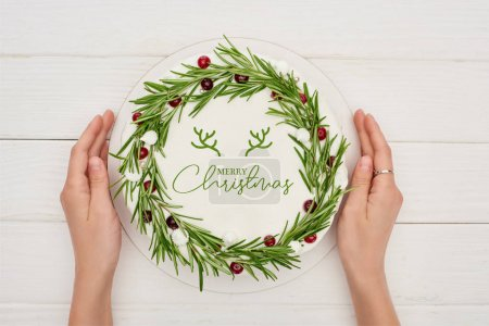 Photo for Cropped view of woman holding christmas pie with Merry Christmas lettering, rosemary and cranberries - Royalty Free Image