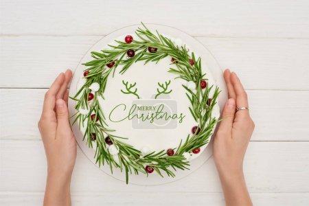 Photo pour Vue recadrée de la femme tenant tarte de Noël avec lettrage Joyeux Noël, romarin et canneberges - image libre de droit