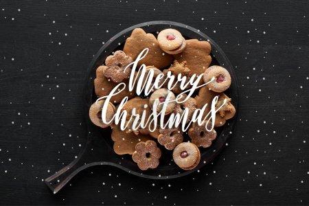 Photo pour Vue du dessus des biscuits de Noël dans une casserole sur une table en bois noir avec illustration Joyeux Noël et chutes de neige - image libre de droit