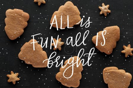 Photo pour Top view of snowflake and Christmas tree cookies on black wooden table with all is fun all is bright illustration - image libre de droit
