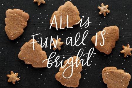 Photo pour Vue de dessus des biscuits de flocon de neige et d'arbre de Noël sur la table en bois noir avec tout est amusant tout est illustration lumineuse - image libre de droit