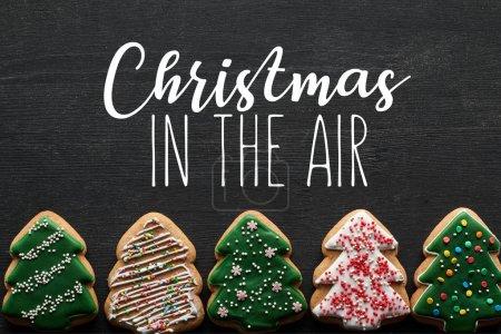 Photo pour Plat étendu avec délicieux biscuits vitrés arbre de Noël sur fond noir avec Noël dans l'air illustration - image libre de droit