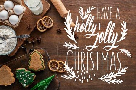 Blick von oben auf leckere Weihnachtsplätzchen in der Nähe von Zutaten und Gewürzen auf Holztisch mit Stechpalme-Schriftzug