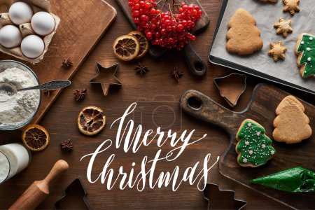 top view of glazed Christmas cookies near ingredients, dough molds and viburnum on wooden table with Merry Christmas illustration