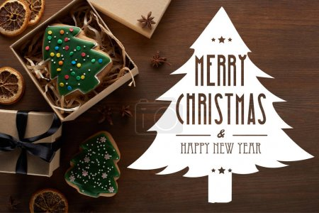Photo for Top view of Christmas tree cookie in gift box on wooden table with Merry Christmas and happy new year illustration - Royalty Free Image