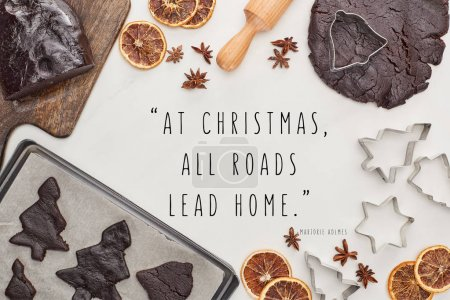 Photo pour Top view of raw dough for chocolate Christmas cookies near ingredients on white background with at Christmas all roads lead home quote - image libre de droit