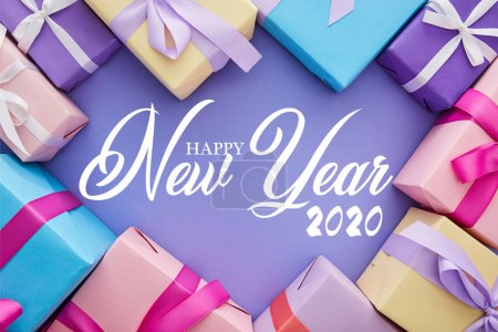 Photo for Top view of colorful presents with bows on purple background with happy new year illustration - Royalty Free Image