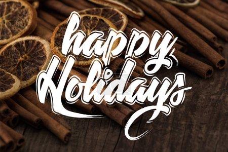Photo pour Vue rapprochée des tranches d'orange séchées et de cannelle sur fond en bois avec illustration joyeuse des fêtes - image libre de droit