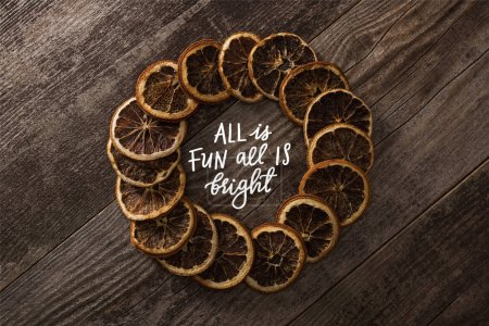 Photo for Round frame of dried orange slices on wooden background with all is fun all is bright lettering - Royalty Free Image