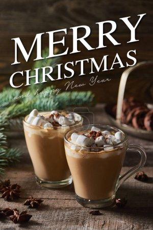 Photo pour Mise au point sélective de cacao avec guimauve et poudre de cacao dans les tasses près des branches de pin, cannelle et anis sur table en bois avec joyeux Noël et joyeux lettrage du nouvel an - image libre de droit