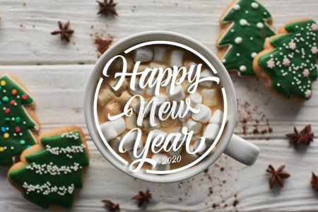 Photo for Top view of Christmas cacao with marshmallow in mug on white wooden table near anise and cookies with happy new year lettering - Royalty Free Image