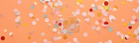 Photo pour Plan panoramique de confettis décoratifs et colorés sur orange - image libre de droit