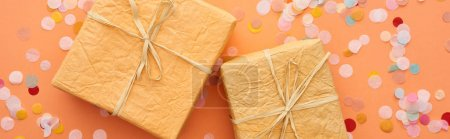 Photo for Panoramic shot of gift boxes with bows near confetti on orange - Royalty Free Image