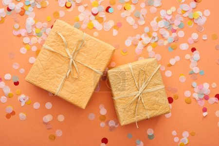 Photo for Top view of gift boxes with bows near confetti on orange - Royalty Free Image