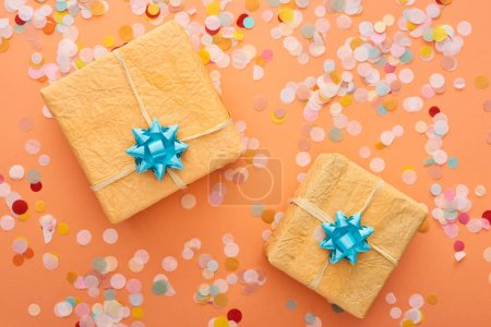 Photo for Top view of blue bows on gift boxes near confetti on orange - Royalty Free Image