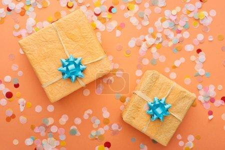 Photo pour Vue du dessus des arcs bleus sur les boîtes cadeaux près de confettis sur orange - image libre de droit